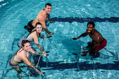 Fitness class doing aqua aerobics on exercise bikes. In swimming pool Royalty Free Stock Photography