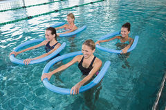 Fitness class doing aqua aerobics with foam rollers stock photo