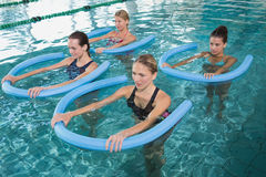 Fitness class doing aqua aerobics with foam rollers. In swimming pool at the leisure centre Royalty Free Stock Images