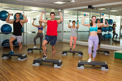 Fitness class doing step aerobics with dumbbells Stock Image