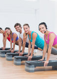 Fitness class doing step aerobics exercise Stock Images