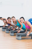 Fitness class doing step aerobics exercise Royalty Free Stock Image