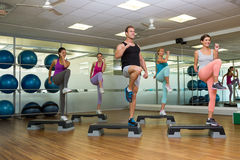 Fitness class doing step aerobics Royalty Free Stock Photography