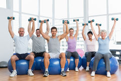 Fitness class with dumbbells sitting on exercise balls in gym Royalty Free Stock Photo