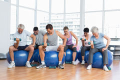 Fitness class with dumbbells sitting on exercise balls in gym Stock Photo