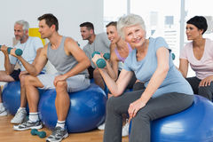 Fitness class with dumbbells sitting on exercise balls in gym Royalty Free Stock Photography