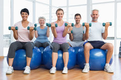 Fitness class with dumbbells sitting on exercise balls Royalty Free Stock Images