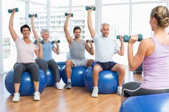 Fitness class with dumbbells sitting on exercise balls Royalty Free Stock Image