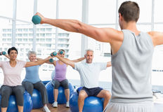Fitness class with dumbbells sitting on exercise balls Stock Images