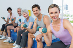 Fitness class exercising with dumbbells in gym Royalty Free Stock Image