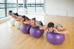 Fitness class exercising on fitness balls in a row Stock Image