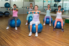 Fitness class holding dumbbells on exercise balls in studio Stock Images