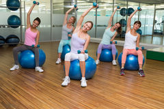 Fitness class holding dumbbells on exercise balls in studio Royalty Free Stock Photos