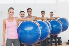 Fitness class holding exercise balls at fitness studio Royalty Free Stock Image