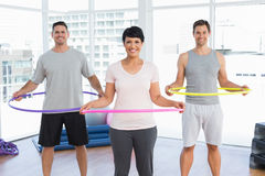 Fitness class holding hula hoops around waist in gym Stock Image
