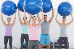 Fitness class holding up exercise balls at the fitness studio Stock Image