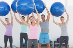 Fitness class holding up exercise balls at fitness studio Stock Photo
