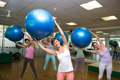Fitness class holding up exercise balls in studio Stock Images