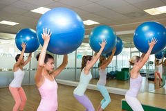 Fitness class holding up exercise balls in studio Royalty Free Stock Image