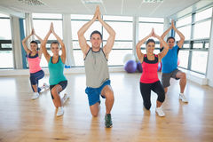 Fitness class and instructor kneeling in Namaste position Royalty Free Stock Image