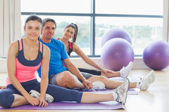 Fitness class and instructor sitting on exercise mats Royalty Free Stock Photo