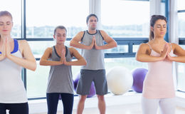 Fitness class and instructor standing in Namaste position Stock Photo