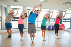 Fitness class and instructor standing in Namaste position Royalty Free Stock Photos