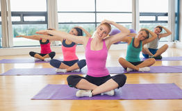 Fitness class and instructor stretching hands on yoga mats Stock Photo