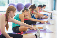 Fitness class and instructor stretching legs Royalty Free Stock Photos