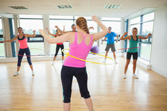 Fitness class and instructor swinging hula hoops at the waist Stock Photos