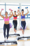 Fitness class performing step aerobics exercise with dumbbells Stock Images