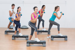Fitness class performing step aerobics exercise with dumbbells Stock Image