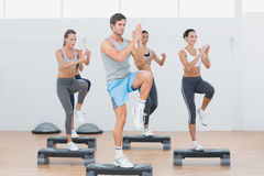 Fitness class performing step aerobics exercise Royalty Free Stock Photos