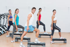 Fitness class performing step aerobics exercise Stock Images