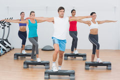 Fitness class performing step aerobics exercise Royalty Free Stock Photo