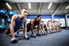 Fitness class in plank position with dumbbells Stock Photos