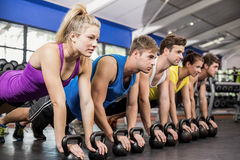 Fitness class in plank position with dumbbells. In gym royalty free stock photos