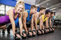 Fitness class in plank position with dumbbells. In gym Stock Photo