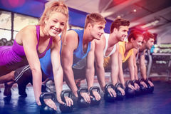 Fitness class in plank position with dumbbells Royalty Free Stock Photo