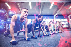Fitness class in plank position with dumbbells. At gym royalty free stock image