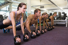 Fitness class in plank position with kettlebells Royalty Free Stock Photo