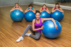 Fitness class posing with exercise balls in studio Royalty Free Stock Image