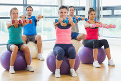 Fitness class sitting with dumbbells on exercise balls Stock Images