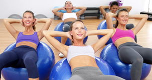 Fitness class sitting on exercise balls doing sit ups stock video