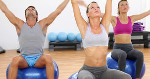 Fitness class sitting on exercise balls stretching. At the gym stock video footage