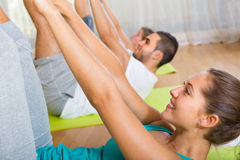 Fitness class in sport club. Group having fitness class in sport club and smiling. Focus on girl Royalty Free Stock Photography