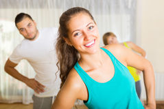 Fitness class in sport club. Young people doing exercises in sport club. Focus on girl Stock Image