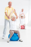 Fitness classes dedicated for senior adults. Photo of two senior couples exercising together, men assisting women on exercise balls Royalty Free Stock Photo