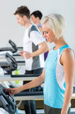 Fitness club woman set-up level on running belt Royalty Free Stock Images