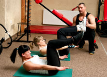 Fitness club women with trainer. Two women exercising in fitness club assisted by professional trainer Stock Photography